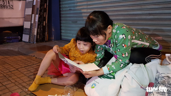 A woman and her daughter read a greeting card gifted by a volunteer on Phan Dang Luu Street in Binh Thanh District, Ho Chi Minh City on December 23, 2019. Photo: Cong Trieu / Tuoi Tre