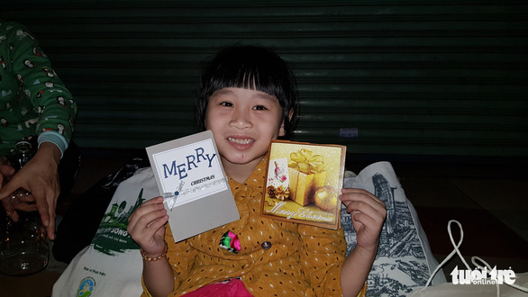 A little girl poses with a greeting card gifted by a volunteer on Phan Dang Luu Street in Binh Thanh District, Ho Chi Minh City on December 23, 2019. Photo: Cong Trieu / Tuoi Tre