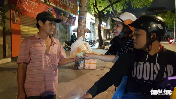 Minh Tuyen (R) gives food to a poor man in Binh Thanh District, Ho Chi Minh City on December 23, 2019. Photo: Cong Trieu / Tuoi Tre