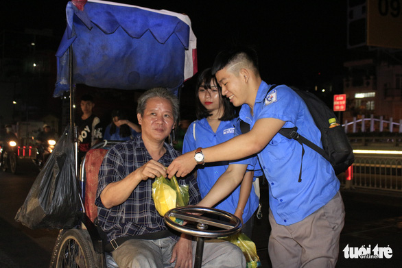 Volunteers give food to a wheelchair-bound man in Ho Chi Minh City on December 23, 2019. Photo: Cong Trieu / Tuoi Tre
