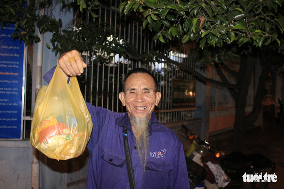 Nguyen Doc, 65, poses with a bag of food given to him by a group of volunteers in Ho Chi Minh City on December 23, 2019. Photo: Cong Trieu / Tuoi Tre