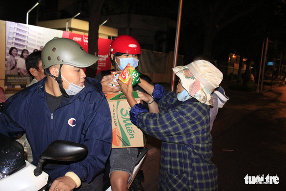 Volunteers give instant noodles to a woman on the street in Ho Chi Minh City on December 23, 2019. Photo: Cong Trieu / Tuoi Tre