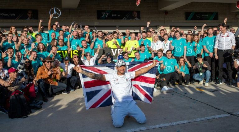 Lewis Hamilton flew the flag with his crew after clinching the Formula 1 title in Texas.