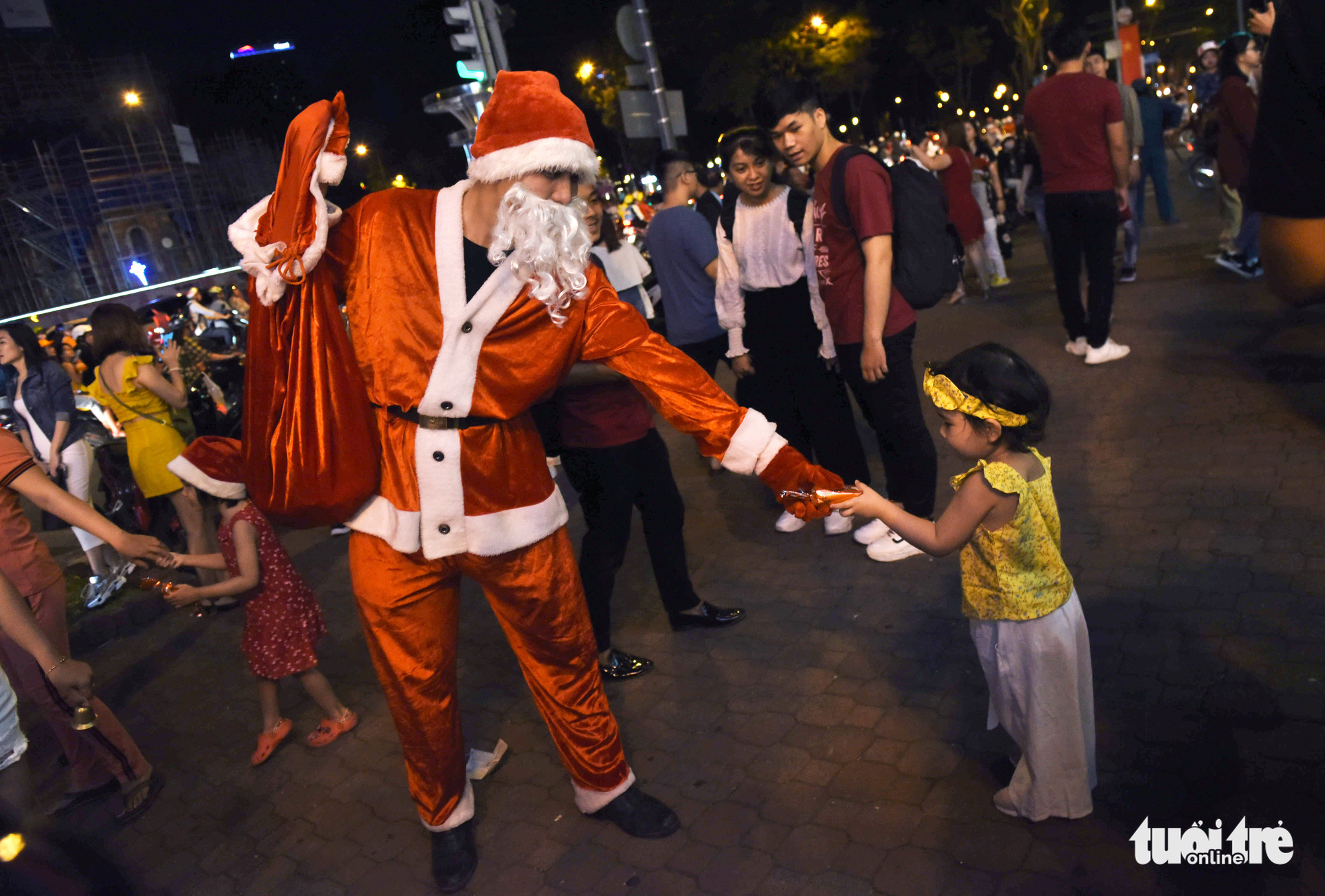 A man dressed as Santa Claus gives a present to a young girl in downtown Ho Chi Minh City on Christmas Eve, December 24, 2019.