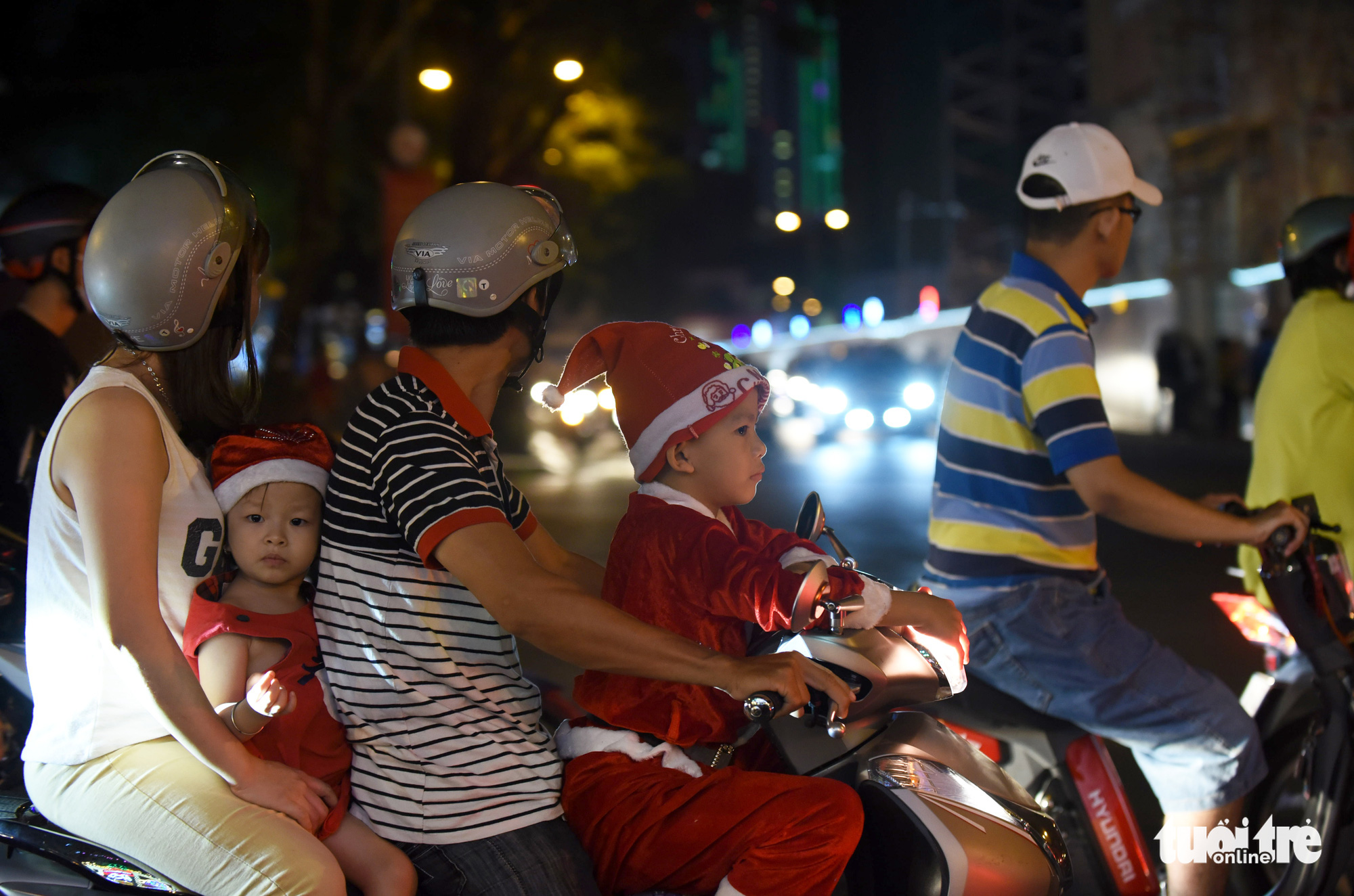 A man carries his family members on a motorbike to celebrate Christmas Eve in downtown Ho Chi Minh City on December 24, 2019.
