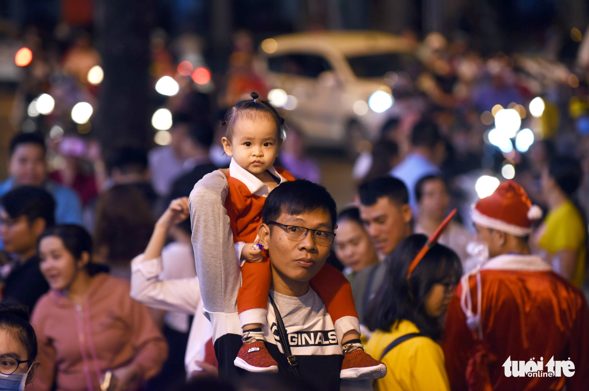 A man carries his daughter on his shoulder through the crowd in Ho Chi Minh City on Christmas Eve, December 24, 2019.