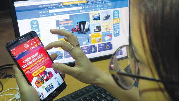 A woman accesses an online shopping site on her smartphone. Photo: Tuoi Tre