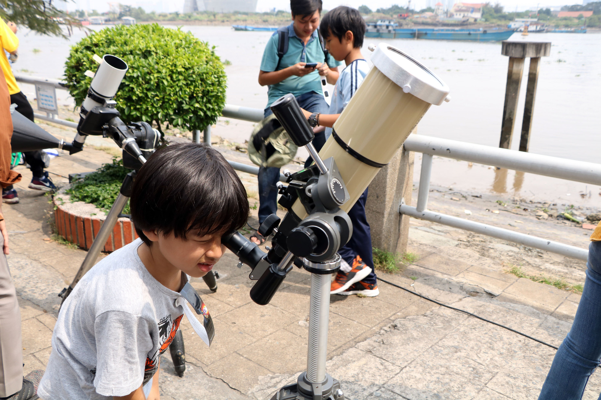 A boy views a solar eclipse through a telescope in Ho Chi Minh City on December 26, 2019. Photo: Trong Nhan / Tuoi Tre