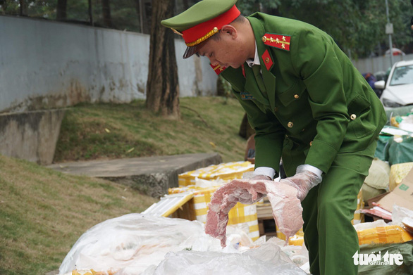 A police officer handles rancid meat. Photo: Xuan Bui