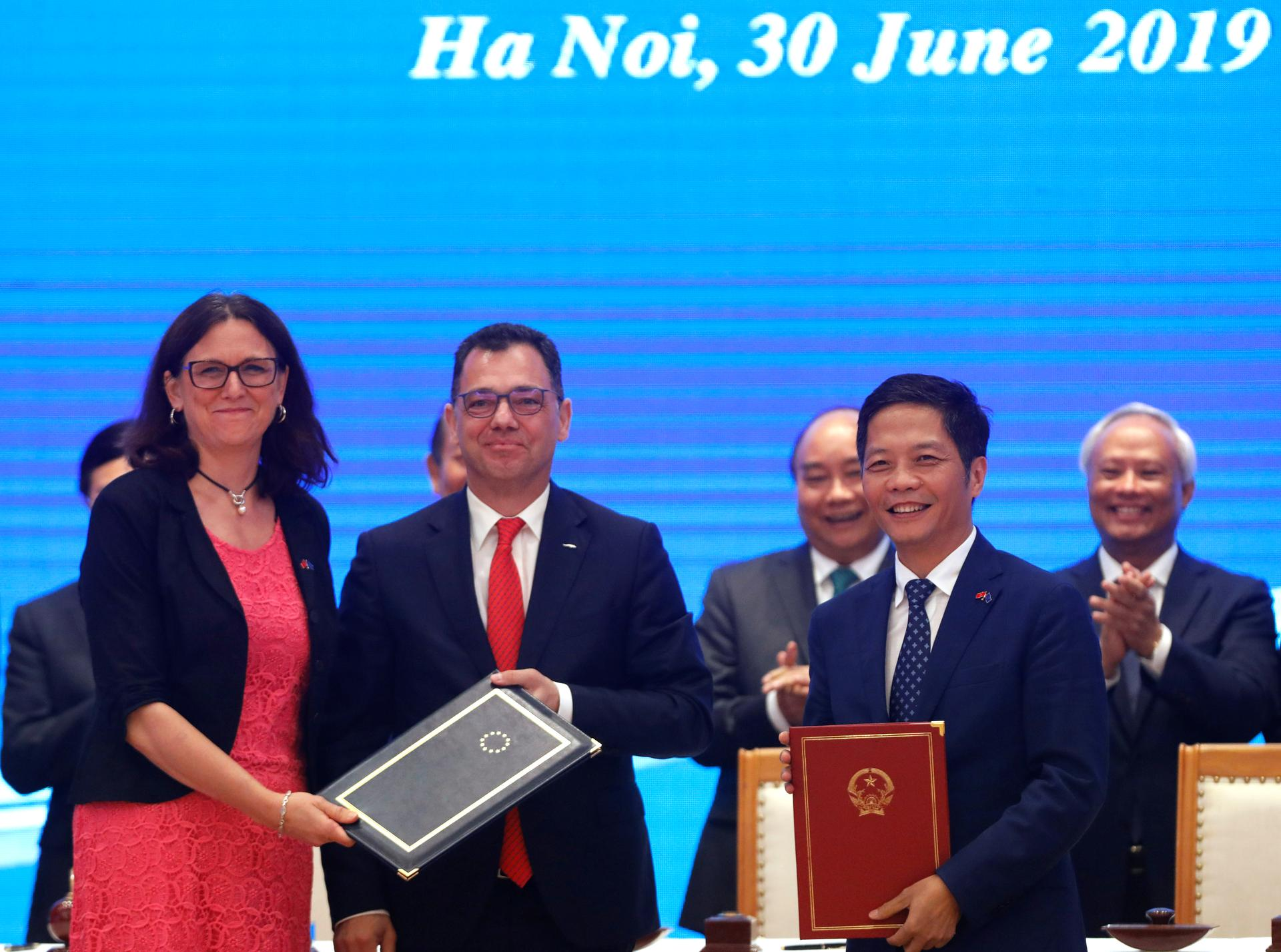 European Commissioner for Trade Cecilia Malmstrom, Romania's Business, Trade and Enterpreneurship Minister Stefan Radu Oprea and Vietnam's Industry and Trade Minister Tran Tuan Anh exchange documents while attending the signing ceremony of EU-Vietnam Free Trade Agreement at the Government Office in Hanoi, Vietnam June 30, 2019. Photo: Reuters