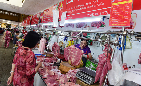 A woman buys pork at a wet market in Ho Chi Minh City. Photo: Quang Dinh / Tuoi Tre