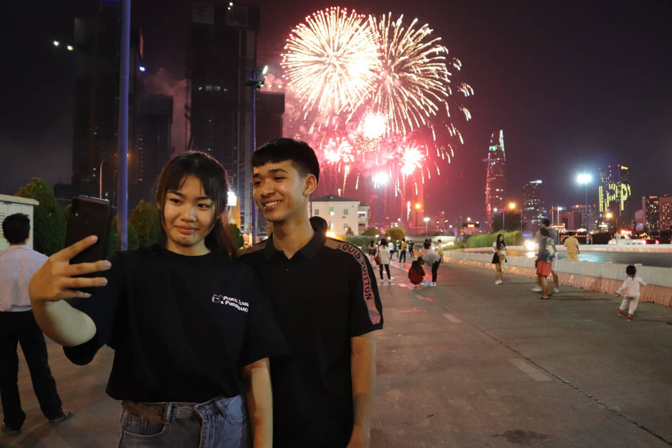 Young Vietnamese take a selfie against the backdrop of fireworks in Ho Chi Minh City, December 31, 2019. Photo: Tuoi Tre