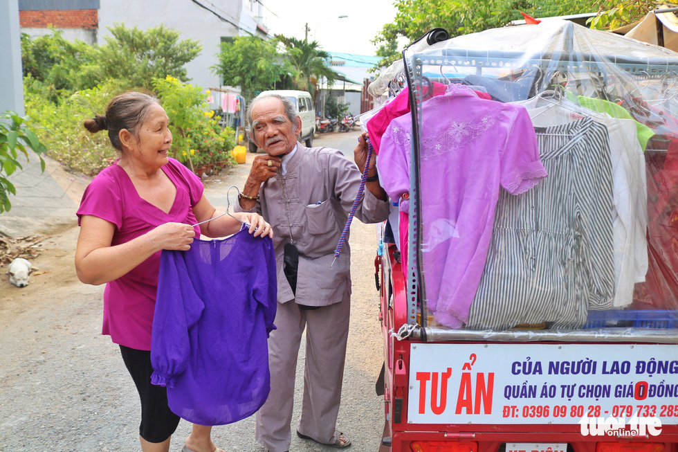 Nguyen Van Tu (R) and Le Thi Be next to their mobile clothing store at an alley on Nguyen Van Tao Street in Nha Be District, Ho Chi Minh City. Photo: Ngoc Phuong / Tuoi Tre