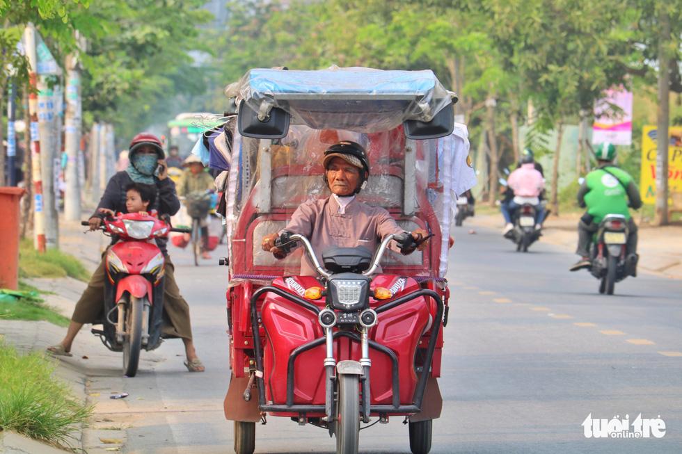 Nguyen Van Tu drives a tuk-tuk offering free clothes in Ho Chi Minh City. Photo: Ngoc Phuong / Tuoi Tre