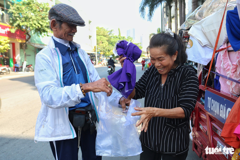Nguyen Van Tu gives free clothes to a woman in Ho Chi Minh City. Photo: Ngoc Phuong / Tuoi Tre