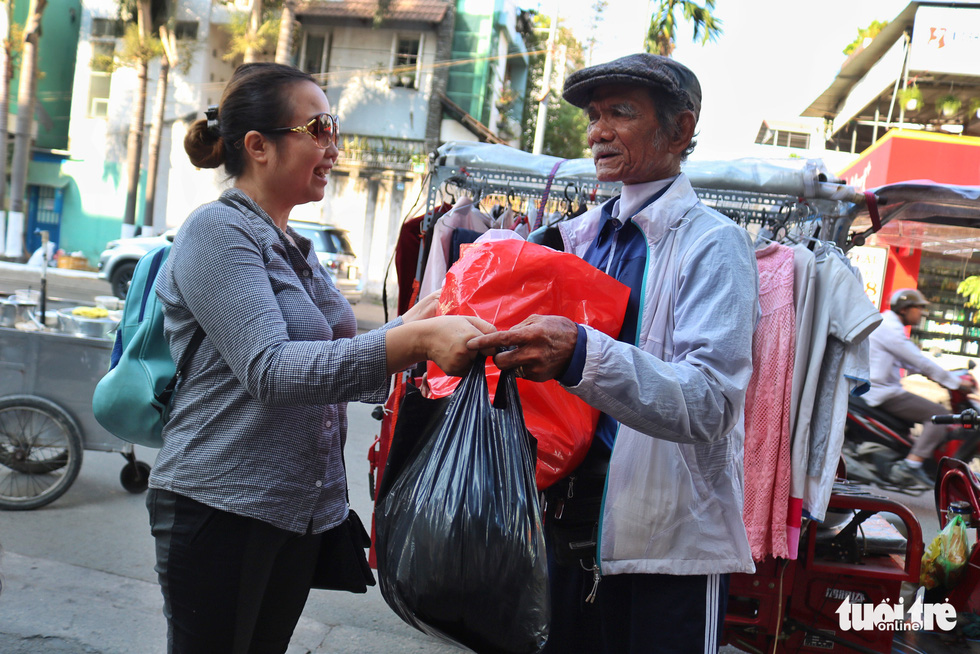 A woman donates her clothes to Nguyen Van Tu's mobile shop. Photo: Ngoc Phuong / Tuoi Tre