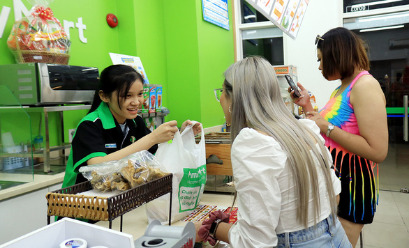 A freshman (L) works as an attendant at a convenience store in District 4, Ho Chi Minh City. Photo: Ngoc Phuong / Tuoi Tre
