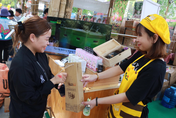 A seller serves a customer with a paper package at the Tet Viet Festival taking place at the Le Van Tam Park in District 1, Ho Chi Minh City, on January 3, 2020. Photo: Ngoc Phuong / Tuoi Tre