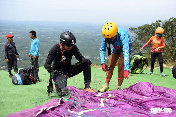 Paragliders check paragliding equipment before a ride. Photo: Tuoi Tre