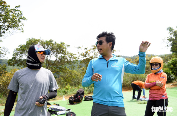 Paragliding instructor Cao Ha Tan (C) reminds players of safety regulations before a ride. Photo: Tuoi Tre