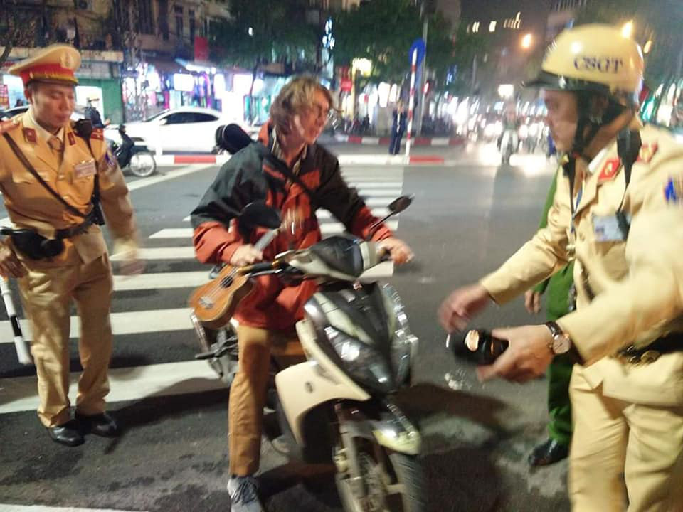 Russian Aleks Ivanov takes his motorbike to the side of the street after being stopped by traffic police in Hanoi on January 7, 2020. Photo: Xuan Bui / Tuoi Tre