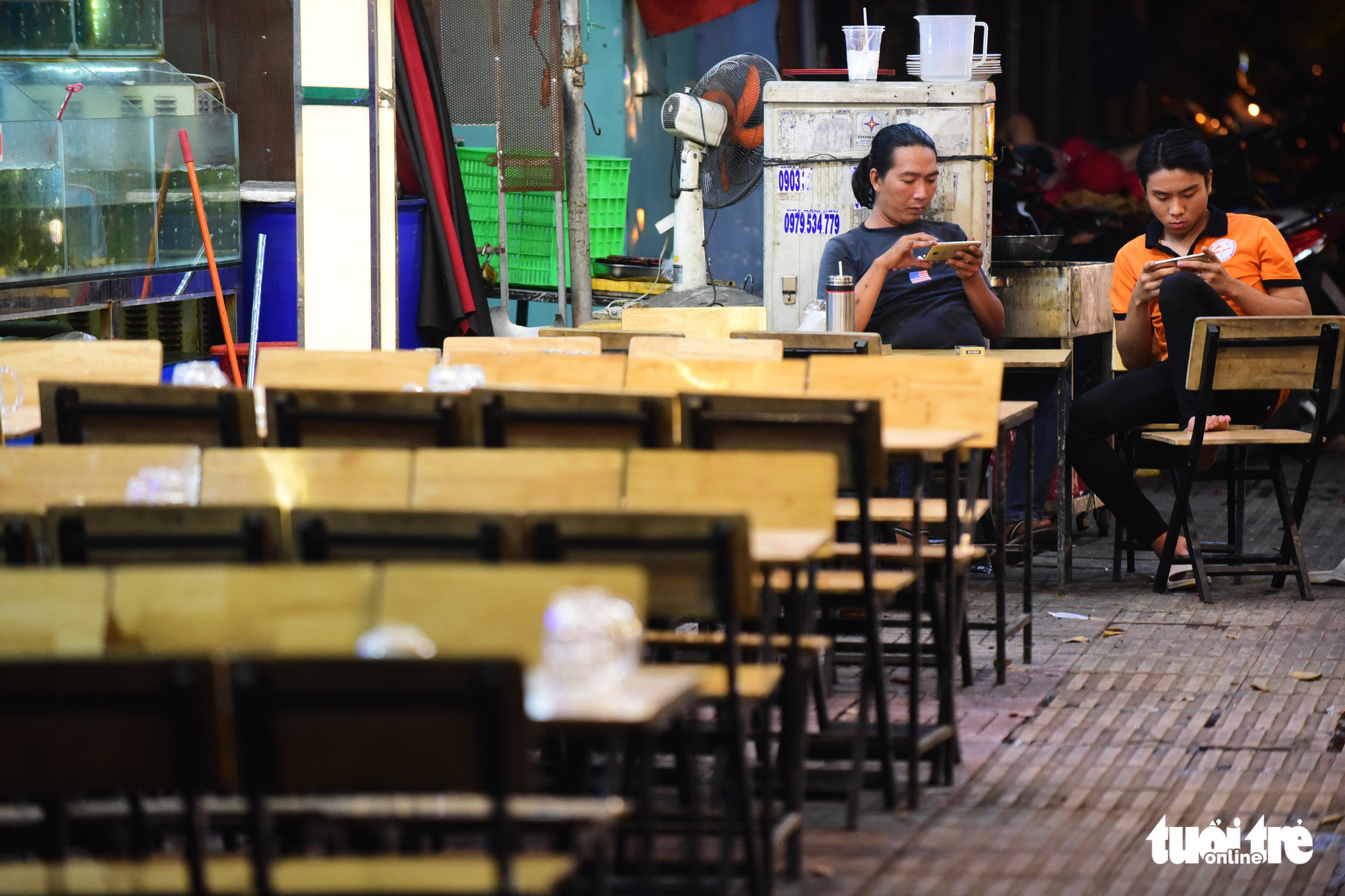 Employees play mobiles games at an empty beer bar in Ho Chi Minh City. Photo: Quang Dinh / Tuoi Tre