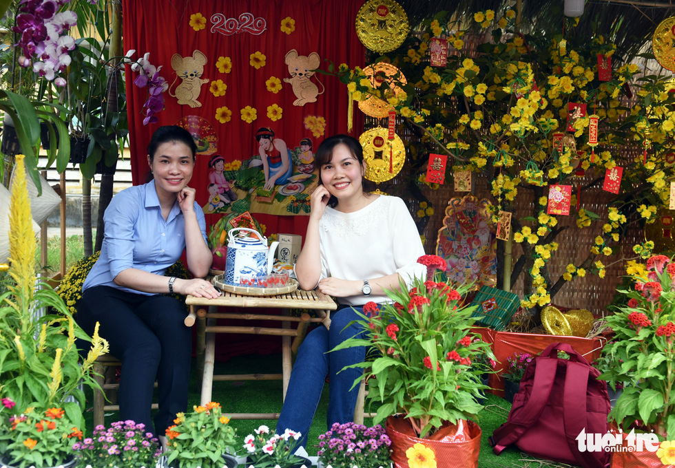 Two women pose for a picture along the 'flower road' at Cho Ray Hospital in Ho Chi Minh City. Photo: Duyen Phan / Tuoi Tre