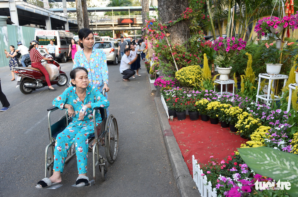 A woman takes her ill mother around the 'flower road' at Cho Ray Hospital in Ho Chi Minh City. Photo: Duyen Phan / Tuoi Tre