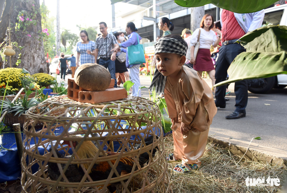A boy looks over a chicken cage along the 'flower road' at Cho Ray Hospital in Ho Chi Minh City. Photo: Duyen Phan / Tuoi Tre