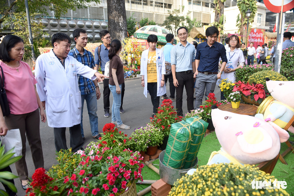 A doctor points at the floral arrangements along the 'flower road' at Cho Ray Hospital in Ho Chi Minh City. Photo: Duyen Phan / Tuoi Tre