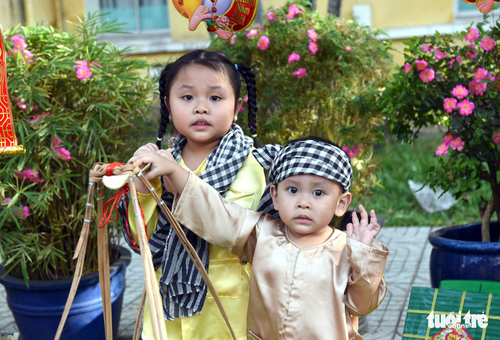 Two kids pose for a picture along the 'flower road' at Cho Ray Hospital in Ho Chi Minh City. Photo: Duyen Phan / Tuoi Tre