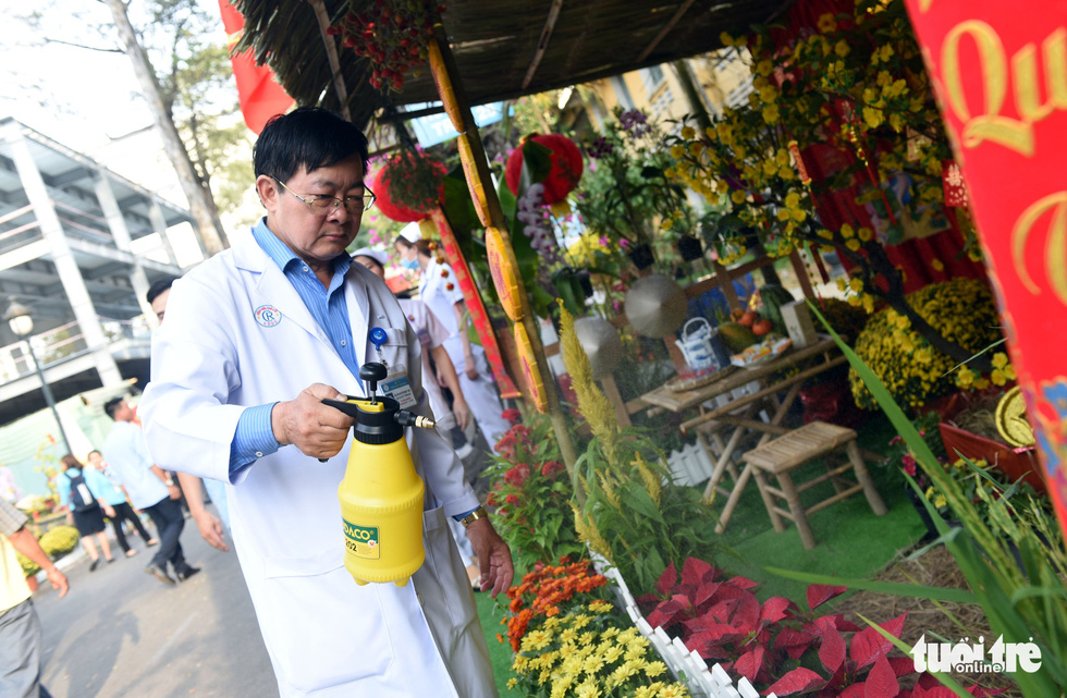 A doctor waters the floral arrangements along the 'flower road' at Cho Ray Hospital in Ho Chi Minh City. Photo: Duyen Phan / Tuoi Tre