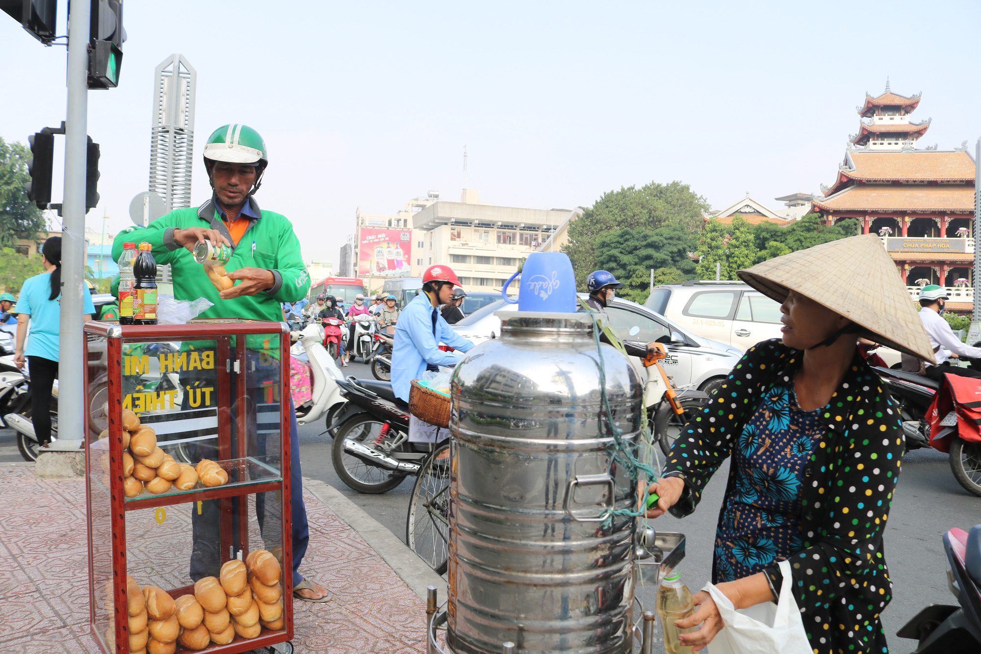 A man prepares a bread as a woman fills her bottle with iced tea at a free bread box donated by college student Nguyen Thi My Dung in Ho Chi Minh City. Photo: Ngoc Phuong / Tuoi Tre