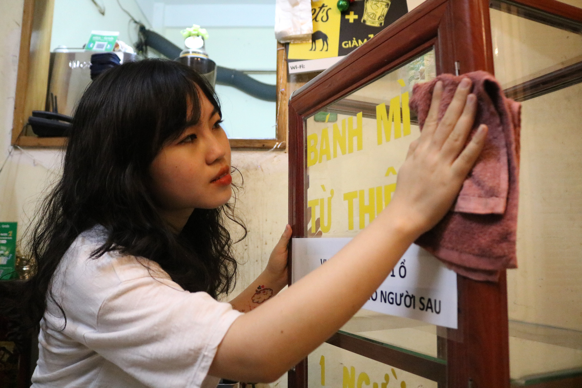College student Nguyen Thi My Dung cleans a container which she uses to store free bread for those in need in Ho Chi Minh City. Photo: Ngoc Phuong / Tuoi Tre