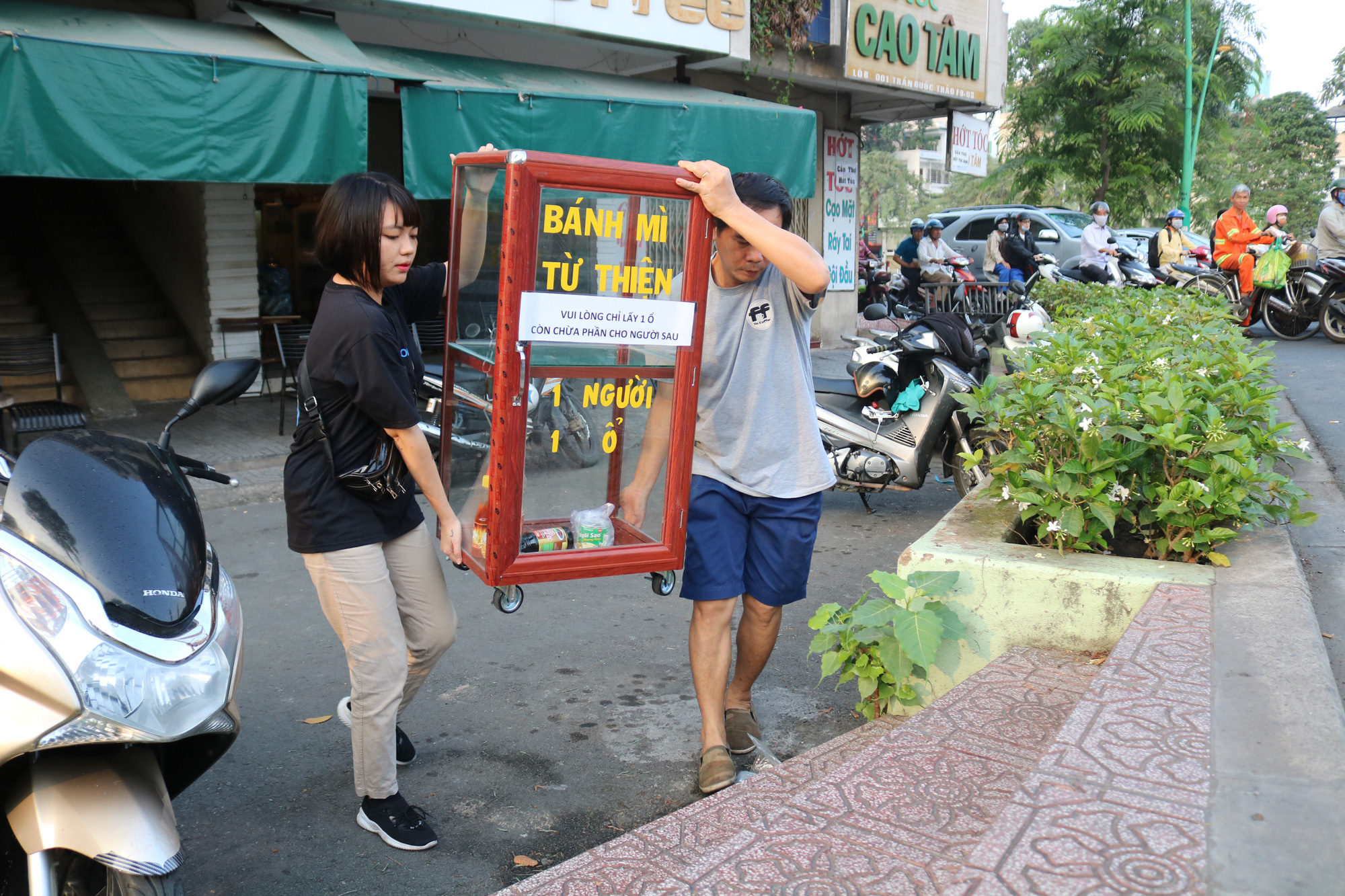Coffee shop manager Dang Tien Tri and his staff carry a charity bread box donated by college student Nguyen Thi My Dung onto the sidewalk in Ho Chi Minh City at 6:30 am in the morning. Photo: Ngoc Phuong / Tuoi Tre