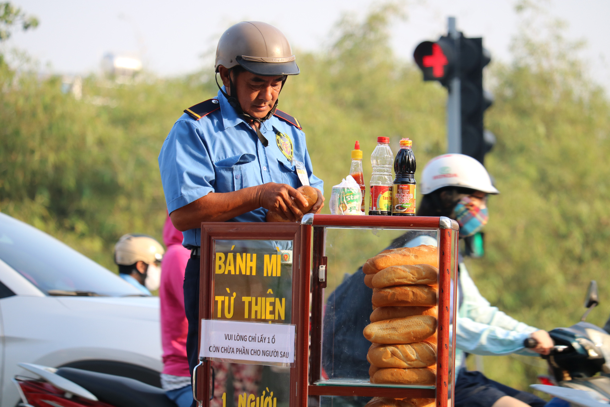 A man prepares his breakfast using bread, condensed milk, soya sauce, and chili sauce available at a charity bread box donated by college student Nguyen Thi My Dung in Ho Chi Minh City. Photo: Ngoc Phuong/ Tuoi Tre