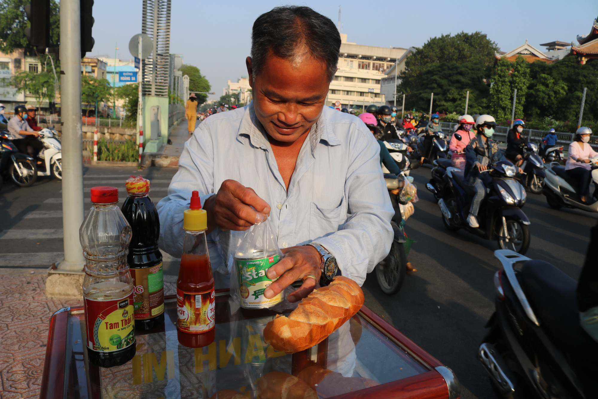 A man restocks condensed milk at a charity bread box donated by college student Nguyen Thi My Dung in Ho Chi Minh City. Photo: Ngoc Phuong / Tuoi Tre