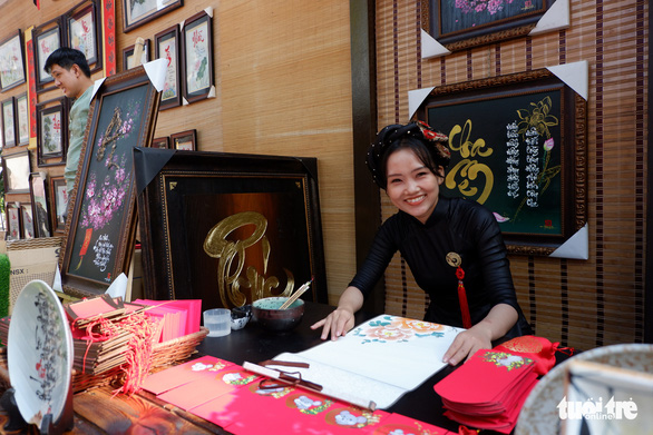 A young lady is performing her calligraphy skills at the Street of Calligraphers. Photo: Kim Anh / Tuoi Tre