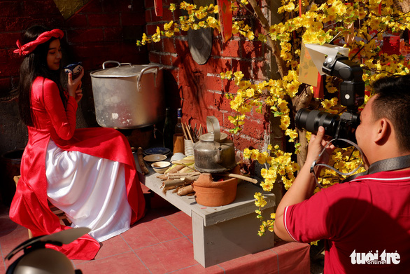 A lady poses for a photo next to the decorative items of the festival. Photo: Kim Anh / Tuoi Tre