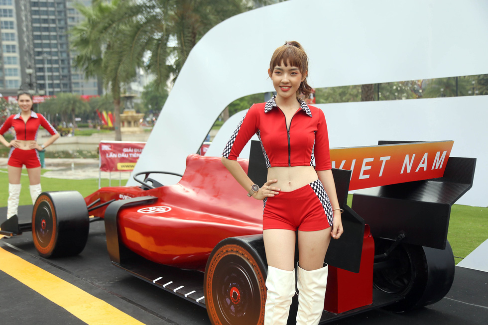 A model poses next to a F1 race car design at the Vinhomes Central Park urban area in Binh Thanh District, Ho Chi Minh City on January 12, 2020. Photo: N.K / Tuoi Tre