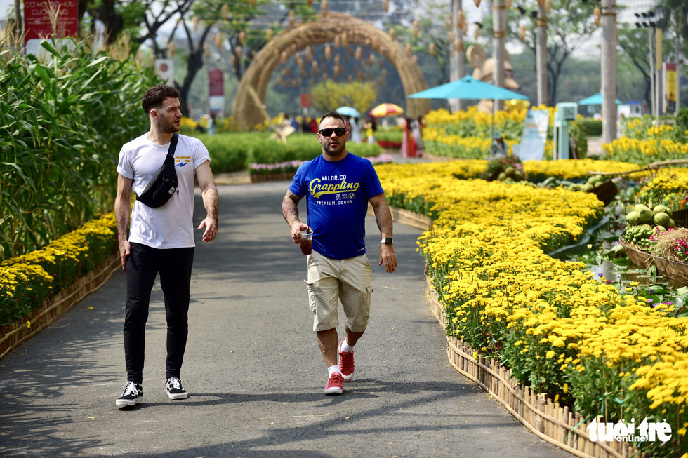 Two foreigners visit the spring flower festival in Phu My Hung, District 7, Ho Chi Minh City. Photo: Quang Dinh / Tuoi Tre