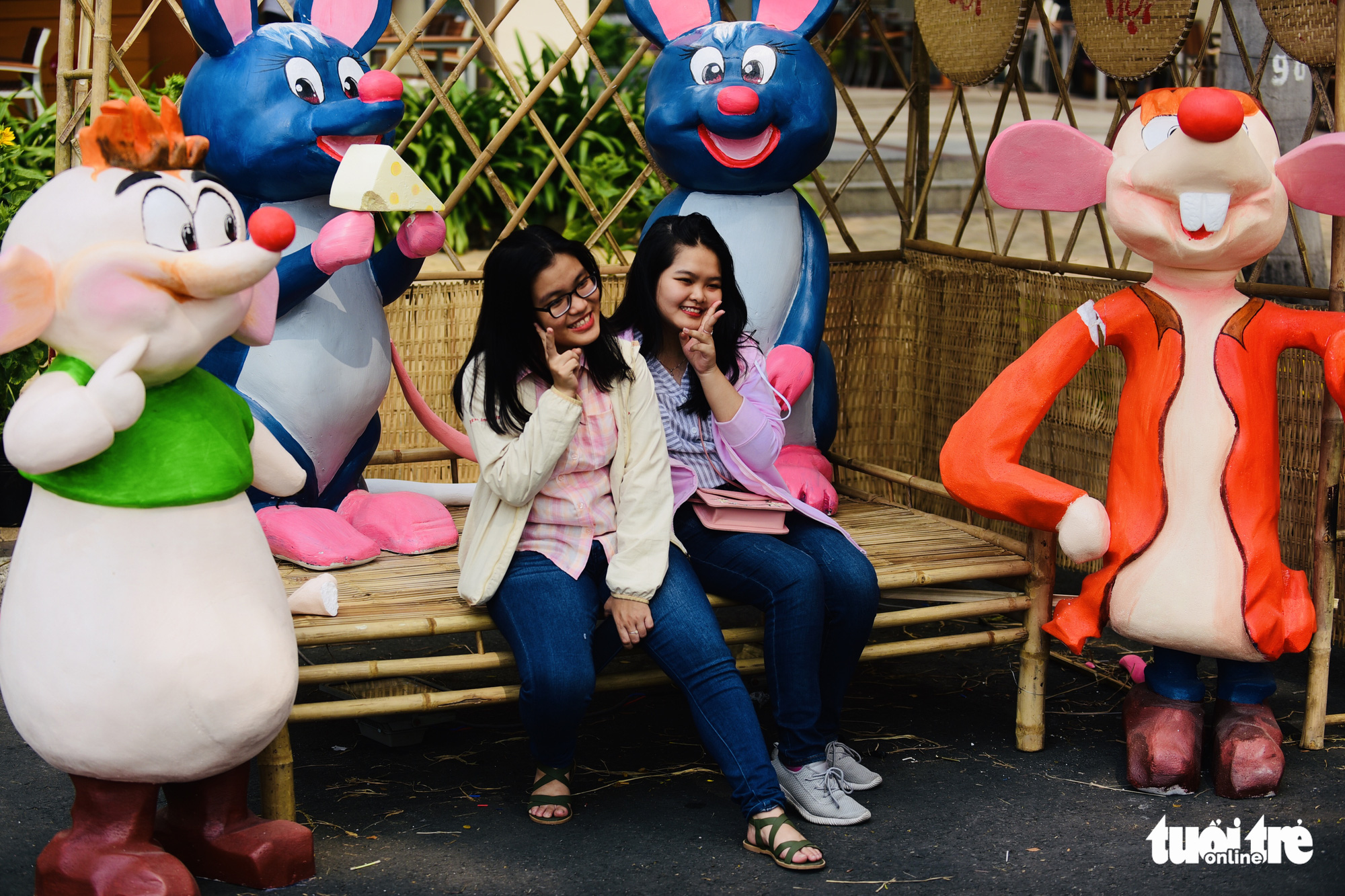 Two girls pose for a photo with rat statues at the spring flower festival in Phu My Hung, District 7, Ho Chi Minh City. Photo: Quang Dinh / Tuoi Tre