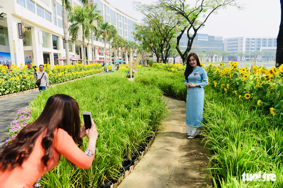 Two women take photos at the spring flower festival in Phu My Hung, District 7, Ho Chi Minh City. Photo: Quang Dinh / Tuoi Tre