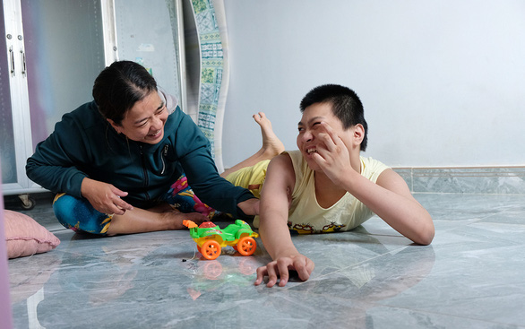 Tran Thi Minh Hanh, a 45-year-old resident in Hoc Mon District, Ho Chi Minh City, and her 17-year-old son, who suffers cerebral palsy. Photo: Vu Thuy / Tuoi Tre