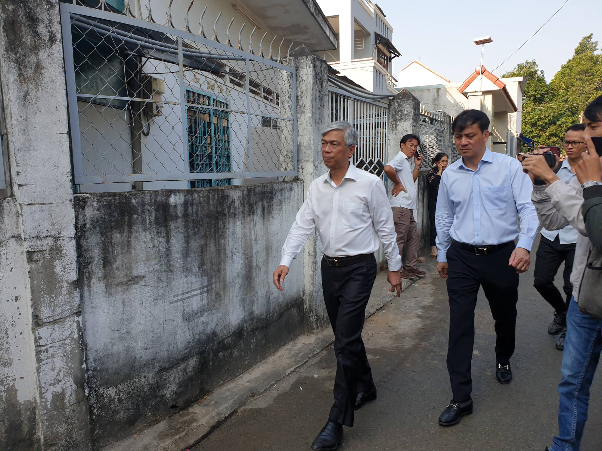 Ho Chi Minh City Deputy Chairman Vo Van Hoan (L) and the municipal Construction Department Director Le Hoa Binh arrive at the site of a house fire that killed five family members on Do Xuan Hop Street in District 9, Ho Chi Minh City on January 21, 2020. Photo: Minh Hoa / Tuoi Tre