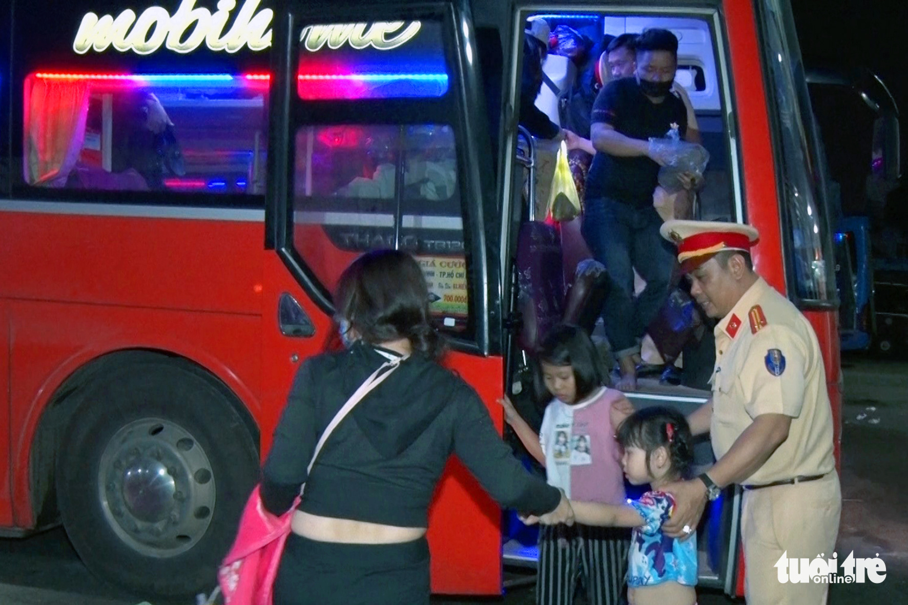 A traffic police officer helps passengers off an overloaded bus in Dong Nai Province, Vietnam on January 21, 2020. Photo: A Loc / Tuoi Tre