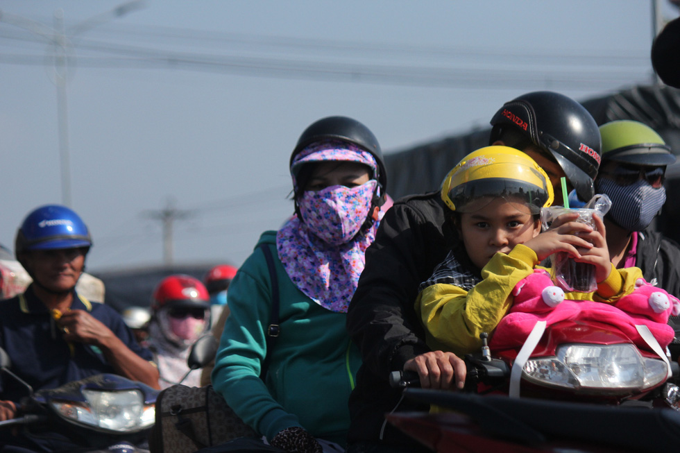A family of three on a motorbike to get back to their hometown on January 22, 2020. Photo: Mau Truong / Tuoi Tre