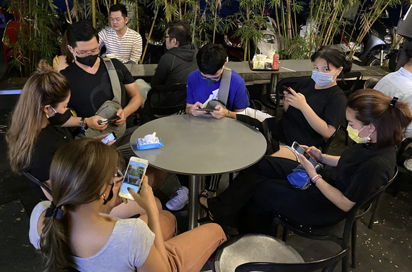 A group of youngsters in Ho Chi Minh City are seen wearing face masks while sitting at a local coffee shop on the night of January 26, 2020. Photo: Tuoi Tre/ Tu Trung