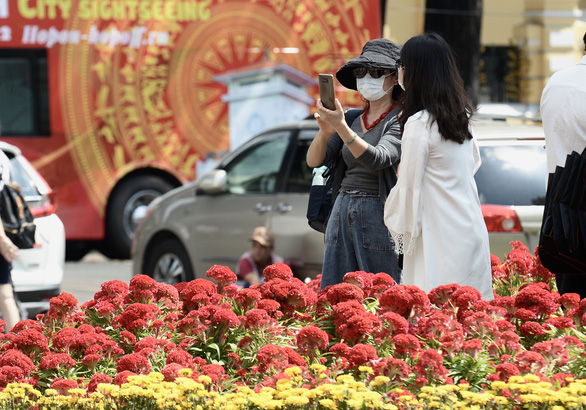 A woman is seen wearing face mask while taking photos with outdoor Tet (Vietnamese Lunar New Year) decorations in Ho Chi Minh City. Photo: Tuoi Tre/Tu Trung