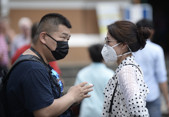 Two people communicate through face masks on the street in Ho Chi Minh City. Photo: Tuoi Tre/ Tu Trung